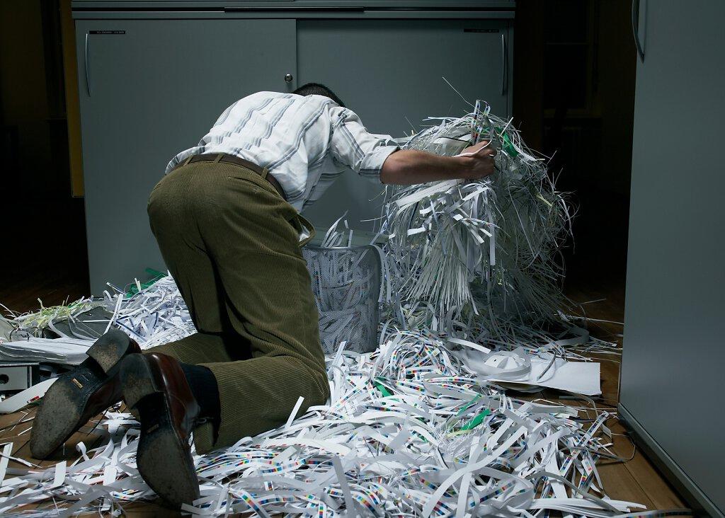 Mann wühlt in Papierschnippsel